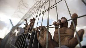 صورة تعبيرية لمجموعة من السجناء يقفون خلال السياج