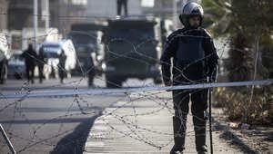 أحد عناصر الشرطة المصرية يحرس حاجزا في شارع بالقاهرة