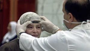 طبيب مصري يقيس درجة حرارة إحدى المريضات