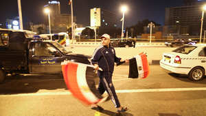 مصري يرفع أعلام بلاده خلال مسيرة تأييد للرئيس السيسي الجمعة