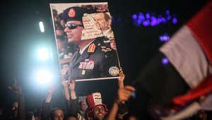 شاب مصري يحمل لافتة تحمل صورة عبد الفتاح السيسي
