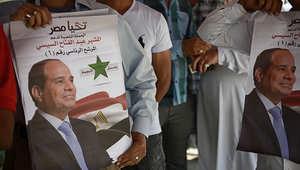 ناخبون مصريون يحملون صور السيسي