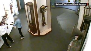 رجل يقوم بتحطيم قطعة فنية داخل متحف للساعات