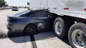 سيارةBMWتعلق تحت شاحنة وهي تسير