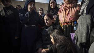 زوجة زياد أبو عين وابنته تجلسان قرب جثمانه قبل دفنه في رام الله.