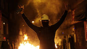 محتج يرفع شارة النصر خلال مظاهرة ليلية ضد الحكومة التركية