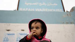 طفل فلسطيني يقف أمام مقر الأونروا في رفح