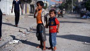 طفلان يقفان في أحد شوارع مخيم النصيرات بمدينة غزة
