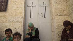 سيدات فلسطينيات يجلسن أمام باب الكنيسة في غزة