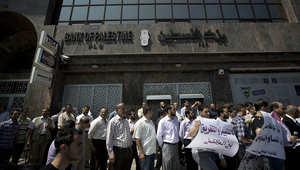 صورة أرشيفية لموظفين فلسطينيين في قطاع غزة يقفون في الطابور بانتظار الحصول على رواتبهم