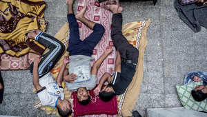 ثلاثة شباب فلسطينيين يفترشون أرضية مدرسة تابعة للأمم المتحدة في بيت حانون