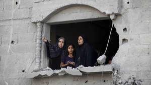 سيدات فلسطينيات ينظرن خارج نافذة منزلهن شبه المدمر في رفح