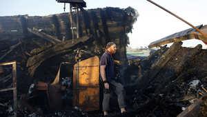 الكندي جون غودفري يتفقد الأضرار التي لحقت بقارب محترق لناشطي سلام بعد اصابته في غارة إسرائيلية