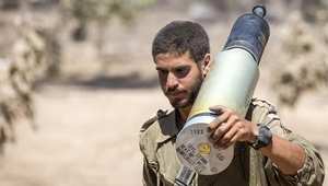 جندي إسرائيل يحمل قذيفة لتذخير مدفع دبابة ميركافا على الشريط الحدودي لغزة 13 يوليو/ تموز 2014