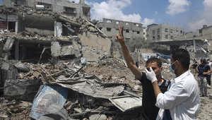 أحد رجال الإنقاذ يسعف رجلا يرفع علامة النصر في حي الشجاعية بغزة