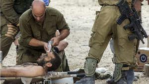 جندي إسرائيلي جريح يتلقى الإسعافات من زملائه في قطاع غزة