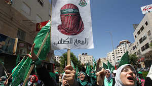 فلسطينيون مؤيدون لحماس يحملون أعلام الحركة الإسلامية وصور قادتها في مظاهرة بالخليل