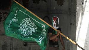 أحد مؤيدي حماس يحمل علم الحركة خلال مظاهرة في الضفة الغربية