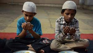 طفلان مسلمان يقومان بالدعاء قبل الإفطار