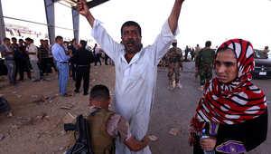 عنصر أمن عراقي يقوم بتفتيش مواطن على أحد الحواجز في مدينة نينوى