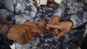 الحبر الانتخابي على أصابع رجال أمن بعد تصويتهم في مدينة كربلاء