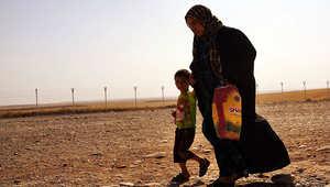 سيدة عراقية تسير برفقة طفلها في أحد مخيمات اللجوء قرب الموصل