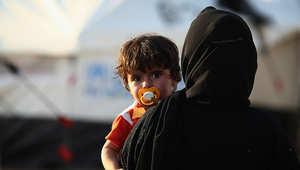 سيدة عراقية تحمل طفلها في أحد مخيمات اللاجئين في العراق