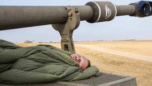 جندي اسرائيلي ينام على مدفع عيار 155 ملم قرب حدود غزة