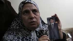 والدة الشاب الفلسطيني معتز حجازي تحمل صورته بعد مقتله صباح الخميس في مواجهات مع الجيش الإسرائيلي بالقدس.