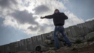 شاب فلسطيني يرمي الحجارة باتجاه الجيش الإسرائيلي قرب حاجز قلنديا