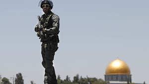 جندي إسرائيلي يقف حارسا فوق إحدى المباني المطلة على قبة الصخرة بالقدس