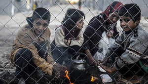مجموعة من الأطفال الأكراد يجلسون حول النار المشتعلة في مخيم للاجئين