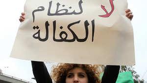 شابة لبنانية تحمل لافتة مناهضة لنظام الكفالة