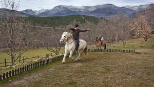 يتمرن جوان، ابن عبدالوحيد، على الرماية من فوق الحصان.