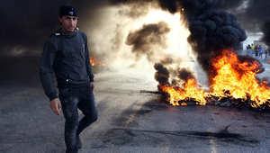 شاب ليبي يمر قرب حريق في الشارع وسط مدينة بنغازي الليبية
