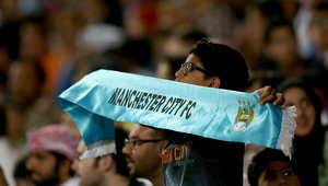 أحد مشجعي مانشستر سيتي يحمل علم النادي خلال إحدى مبارياته
