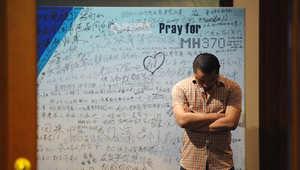 رجل يتلو صلوات قرب ملصق يدعو لسلامة عودة الطائرة المفقودة