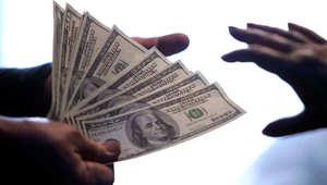 صورة تعبيرية لتسليم نقود