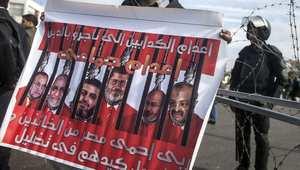 لافتة تحمل صور محمد مرسي وأعضاء جماعة الإخوان المسلمين خلف القضبان