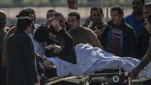 مبارك يحي الأشخاص من حوله بعد نقله من المروحية العسكرية إلى سيارة إسعاف