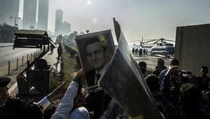 أنصار مبارك يرفعون صوره فيما تستعد مروحية طبية لنقل الرئيس المصري الأسبق من مستشفى المعادي العسكري إلى قاعة المحكمة