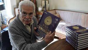 """عمر الشريف يحمل كتاب """"ألف اختراع واختراع"""""""
