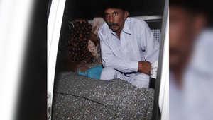 محمد إقبال، زوج المرأة المقتولة، فرزانة بارفين، يجلس إإلى جانب جثة زوجته التي كانت حاملاً بالشهر الثالث وحوله أقاربها