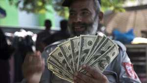فلسطيني موظف بحكومة حماس السابقة يستعرض دولارات بعد تلقيه جانبا من راتبه المتأخر لعدة أشهر
