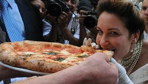 ممثلة ترتدي زي الملكة مارغريتا وتتناول البيتزا المسماه باسمها في احتفال بمدينة نابولي