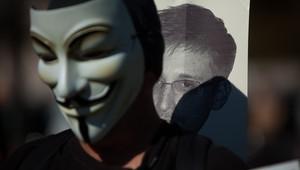 متظاهر يضع قناع فانديتا أمام صورة لسنودن