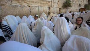 مجموعة من المتدينين اليهود يجلسون قرب حائط المبكى في القدس
