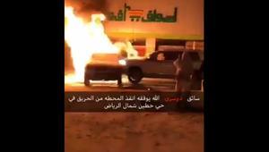 سعودي يدفع مركبة محترقة بعيداً عن محطة الوقود