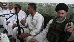 رجل دين شيعي يحمل سلاحه بمركز للمتطوعين في ديالى