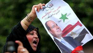 سيدة مصرية تحمل ملصقا مؤيدا للسيسي